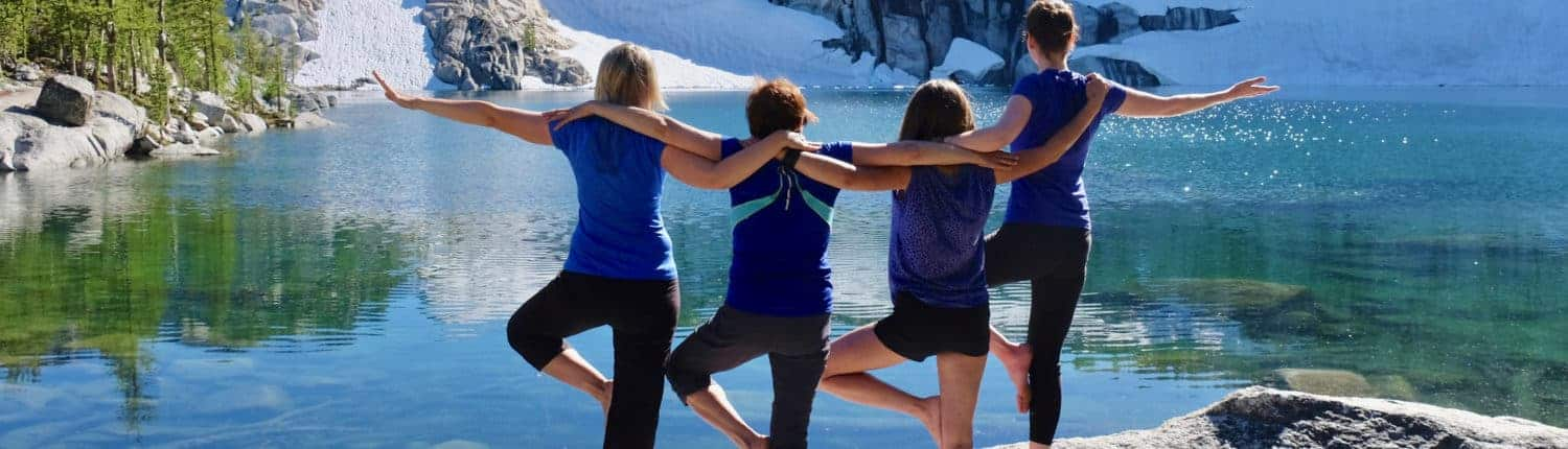 Group of happy friends in yoga pose by beautiful lake.